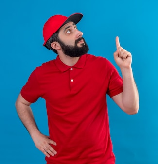 Beeindruckter junger gutaussehender kaukasischer lieferbote, der rote uniform und mütze trägt, die hand auf taille setzt und lokal auf blau zeigt