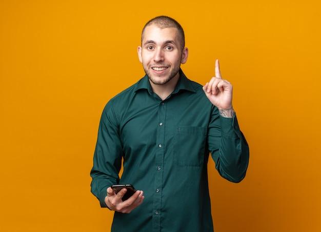 Beeindruckter junger gutaussehender kerl, der ein grünes hemd trägt, das telefonpunkte nach oben hält