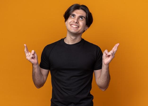 Beeindruckter junger gutaussehender kerl mit schwarzem t-shirt, das die finger isoliert auf oranger wand kreuzt