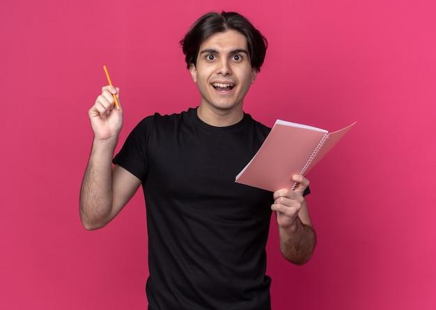 Beeindruckter junger gutaussehender kerl mit schwarzem t-shirt, der ein notizbuch mit bleistift hält - isoliert auf rosa wand