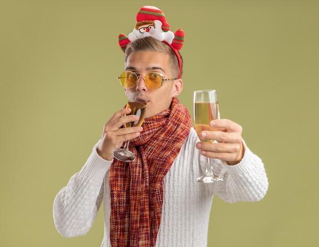 Beeindruckter junger gutaussehender kerl mit weihnachtsmann-stirnband und -schal, der zwei gläser champagner hält, einen trinkt und einen anderen in richtung kamera ausstreckt, isoliert auf olivgrüner wand?