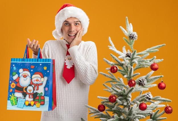 Beeindruckter junger gutaussehender kerl mit weihnachtsmütze und weihnachtsmann-krawatte, der in der nähe des geschmückten weihnachtsbaums steht und weihnachtsgeschenktüten hält, die hand auf das gesicht legen und isoliert auf oranger wand aussehen