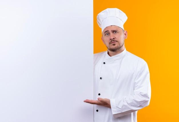 Beeindruckter junger gutaussehender koch in kochuniform, der hinter weißer wand steht und auf ihn isoliert auf oranger wand mit kopierraum zeigt