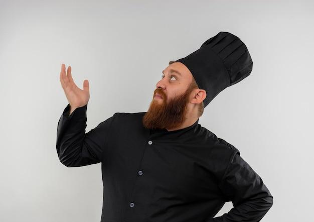 Beeindruckter junger gutaussehender koch in kochuniform, der leere hand zeigt und isoliert auf weißer wand nach oben schaut