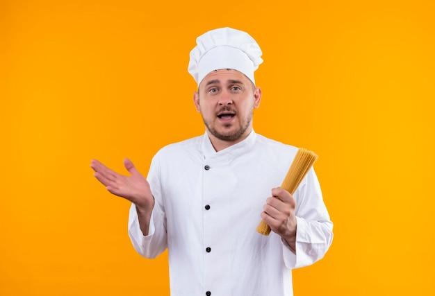 Beeindruckter junger gutaussehender koch in kochuniform, der spaghetti-nudeln hält und leere hand isoliert auf oranger wand zeigt