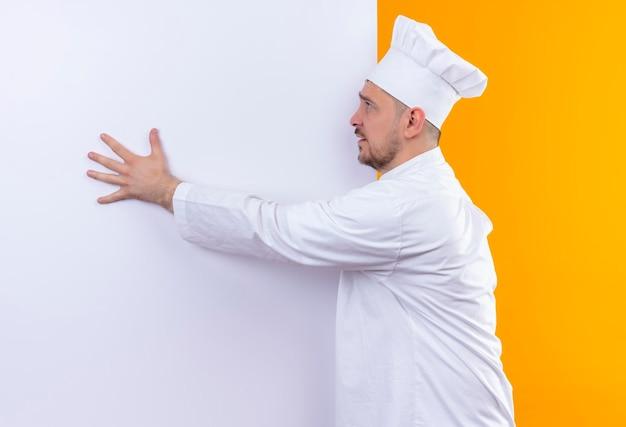 Beeindruckter junger, gutaussehender koch in kochuniform, der vor einer weißen wand steht und die hand darauf legt, die seite isoliert auf der orangefarbenen wand zu betrachten