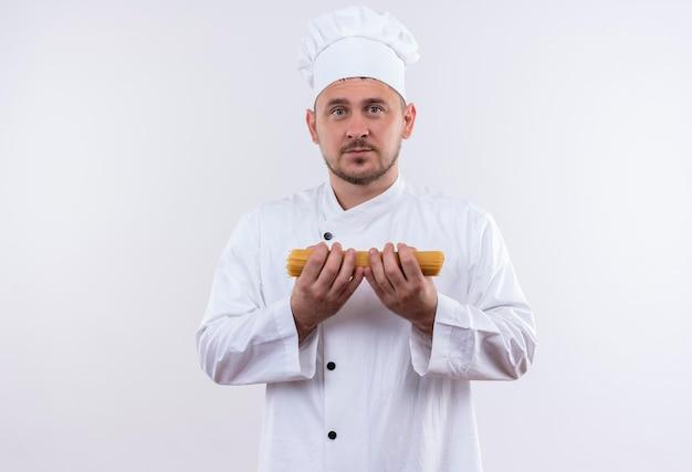 Beeindruckter junger gutaussehender koch in kochuniform mit spaghetti-nudeln isoliert auf weißer wand
