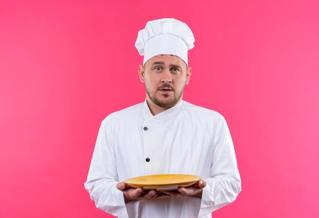 Beeindruckter junger gutaussehender koch in kochuniform mit teller isoliert auf rosa wand
