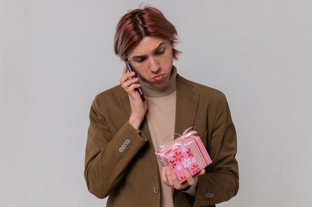 Beeindruckter junger gutaussehender mann, der am telefon spricht und geschenkbox betrachtet