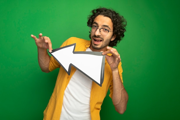Beeindruckter junger gutaussehender mann, der eine brille hält, die pfeilmarkierung hält, die zur seite zeigt, die vorne lokalisiert auf grüner wand betrachtet