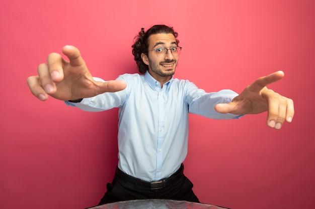 Beeindruckter junger gutaussehender mann, der eine brille trägt, die nach vorne lächelt und sie tut geste lokalisiert auf rosa wand