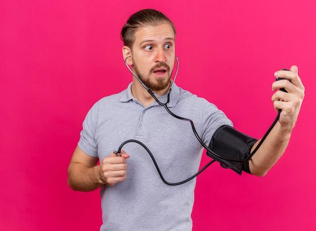 Beeindruckter junger gutaussehender slawischer kranker mann, der stethoskop trägt, das seinen druck mit blutdruckmessgerät misst, das isoliert auf rosa wand mit kopienraum betrachtet