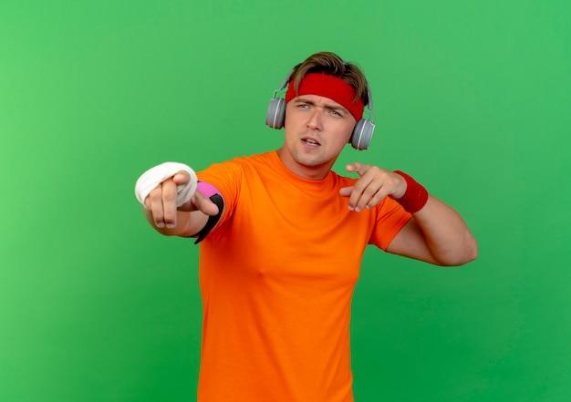 Beeindruckter junger gutaussehender sportlicher mann, der stirnband und armbänder und kopfhörer und telefonarmband mit verletztem handgelenk trägt, das mit verband gewickelt ist, der auf grün zeigt und seite betrachtet