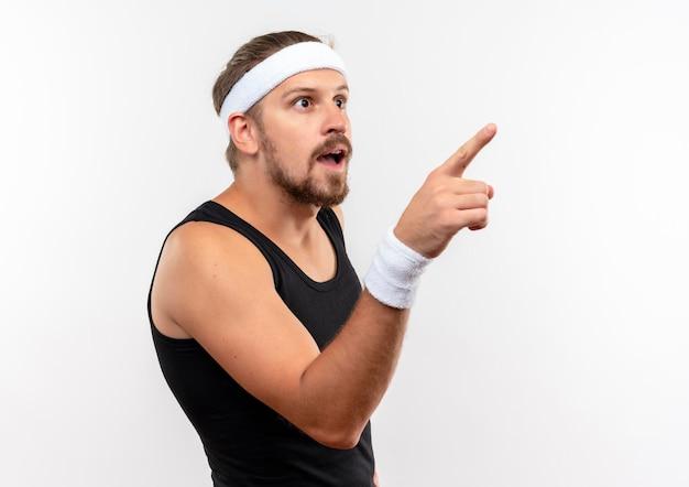 Beeindruckter junger, gutaussehender, sportlicher mann mit stirnband und armbändern, der auf die seite zeigt und auf die weiße wand mit kopienraum blickt?