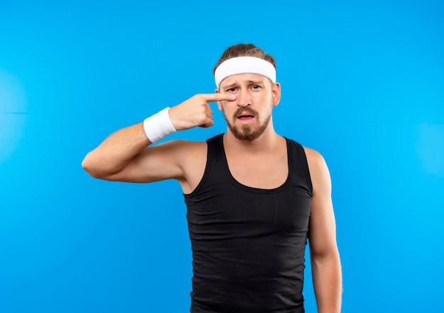 Beeindruckter junger, gutaussehender, sportlicher mann mit stirnband und armbändern, der auf seine nase zeigt, isoliert auf blauer wand