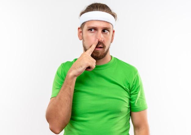 Beeindruckter junger, gutaussehender, sportlicher mann mit stirnband und armbändern, der den finger auf die nase legt und die seite isoliert auf weißer wand betrachtet