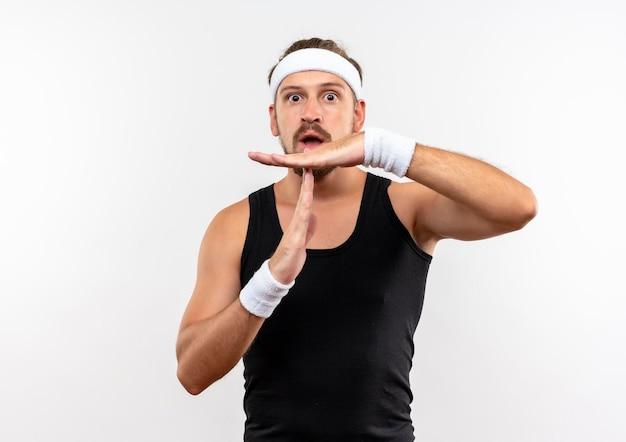 Beeindruckter junger, gutaussehender, sportlicher mann mit stirnband und armbändern, der eine timeout-geste isoliert auf weißer wand mit kopierraum macht