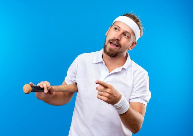 Beeindruckter junger, gutaussehender, sportlicher mann mit stirnband und armbändern, der einen baseballschläger hält und auf die seite isoliert auf blauer wand zeigt