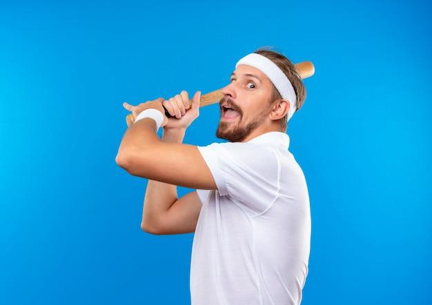 Beeindruckter junger, gutaussehender, sportlicher mann mit stirnband und armbändern, der einen baseballschläger hält und sich bereit macht, den ball isoliert auf blauer wand zu schlagen