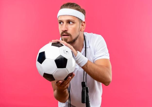 Beeindruckter junger, gutaussehender, sportlicher mann mit stirnband und armbändern, der fußball hält und seitlich mit springseil um den hals isoliert auf rosa wand schaut