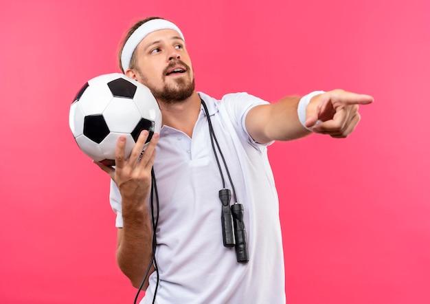 Beeindruckter junger, gutaussehender, sportlicher mann mit stirnband und armbändern, der fußball zur seite hält und gerade mit springseil um den hals zeigt, isoliert auf rosa wand