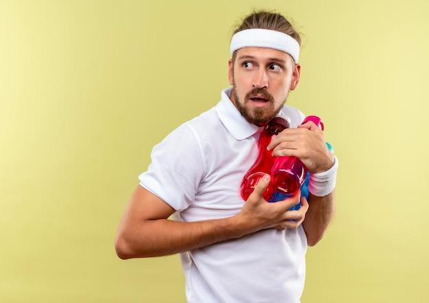 Beeindruckter junger, gutaussehender, sportlicher mann mit stirnband und armbändern, der wasserflaschen hält und seitlich isoliert auf grüner wand mit kopierraum schaut