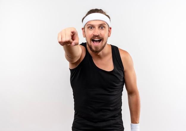 Beeindruckter junger, gutaussehender, sportlicher mann mit stirnband und armbändern, die isoliert auf weiße wand mit kopierraum zeigen