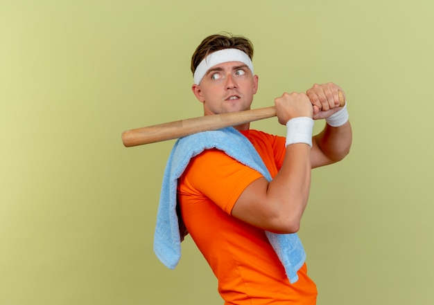 Beeindruckter junger, gutaussehender, sportlicher mann mit stirnband und armbändern mit handtuch auf der schulter, der in der profilansicht steht und einen baseballschläger auf der schulter hält, der nach hinten schaut