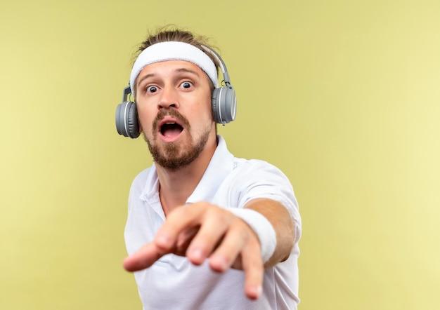 Beeindruckter junger, gutaussehender, sportlicher mann mit stirnband und armbändern und kopfhörern, der die hand in richtung isoliert auf grüner wand mit kopierraum ausstreckt