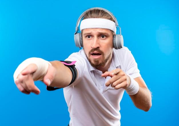 Beeindruckter junger, gutaussehender, sportlicher mann mit stirnband und armbändern und kopfhörern mit armbinde, der auf die seite isoliert auf blauer wand zeigt