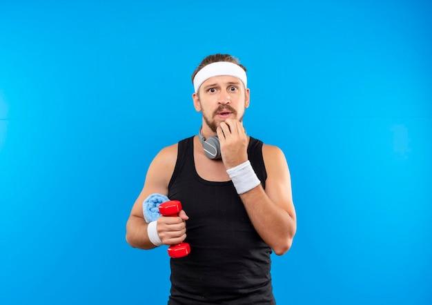 Beeindruckter junger, gutaussehender, sportlicher mann mit stirnband und armbändern und kopfhörern um den hals, der hantel mit handtuch hält und hand auf das kinn legt, isoliert auf blauer wand mit kopierraum