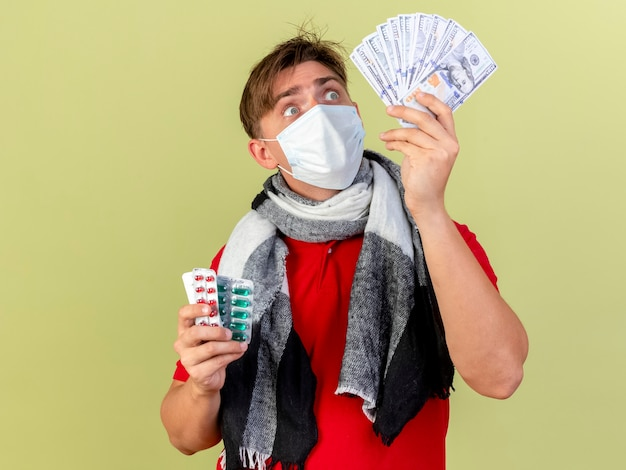 Beeindruckter junger hübscher blonder kranker mann, der maske hält, die geld und packungen der medizinischen pillen hält, die geld lokalisiert auf olivgrüner wand betrachten