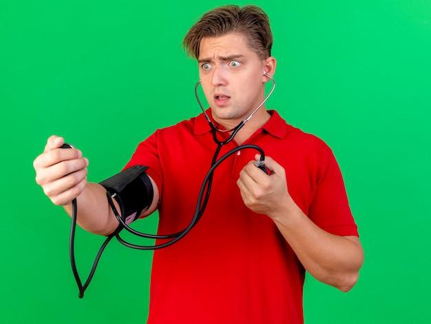 Beeindruckter junger hübscher blonder kranker mann, der stethoskop trägt, das druck auf sich selbst misst und blutdruckmessgerät auf grüner wand isoliert betrachtet