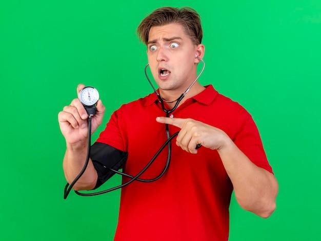 Beeindruckter junger hübscher blonder kranker mann, der stethoskop trägt, das druck zu sich selbst hält, das betrachten und zeigen auf blutdruckmessgerät lokalisiert auf grüner wand