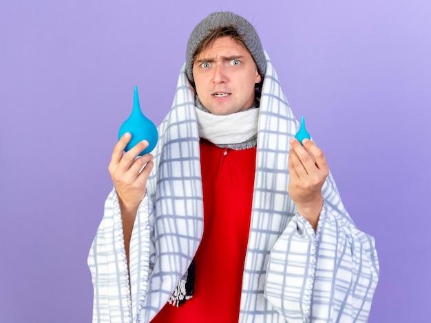 Beeindruckter junger hübscher blonder kranker mann, der wintermütze und schal trägt, die in plaid eingewickelt sind, das einläufe hält, die kamera lokalisiert auf lila hintergrund betrachten