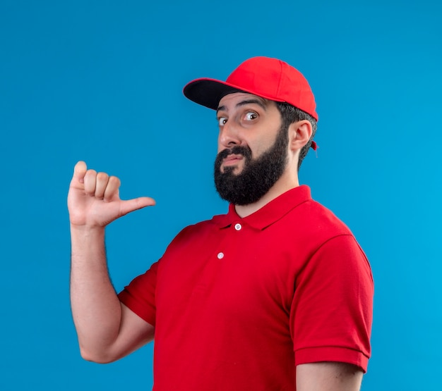 Beeindruckter junger hübscher kaukasischer lieferbote, der rote uniform und kappe trägt, die auf blau auf sich zeigen