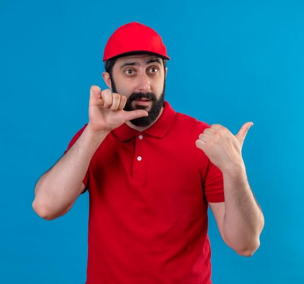 Beeindruckter junger hübscher kaukasischer lieferbote, der rote uniform und kappe trägt, die gerade schauen und auf seite zeigen, die auf blau lokalisiert wird