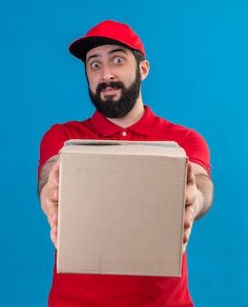 Beeindruckter junger hübscher kaukasischer lieferbote, der rote uniform und kappe trägt, die karton in richtung kamera streckt, die auf blau lokalisiert wird