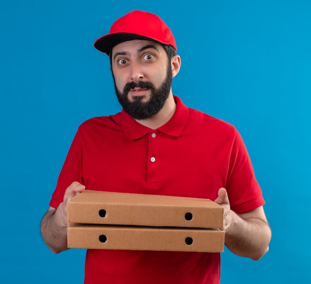 Beeindruckter junger hübscher kaukasischer lieferbote, der rote uniform und kappe trägt, die pizzakästen lokalisiert auf blau hält