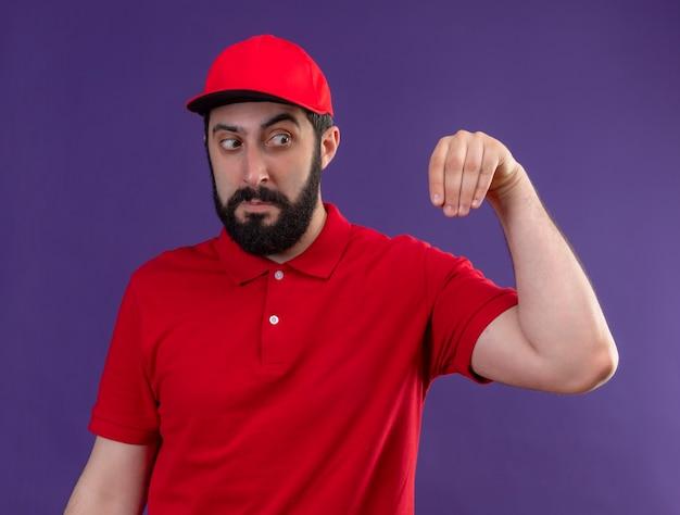 Beeindruckter junger hübscher kaukasischer lieferbote, der rote uniform und mütze trägt, tut so, als würde er etwas halten und seine auf lila isolierte hand betrachten Kostenlose Fotos