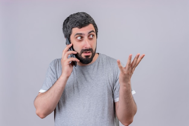 Beeindruckter junger hübscher kaukasischer mann, der am telefon spricht, das seite betrachtet und leere hand lokalisiert auf weiß mit kopienraum zeigt