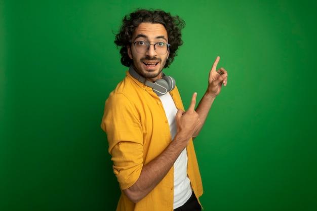 Beeindruckter junger hübscher kaukasischer mann, der brille mit kopfhörern um den hals steht, der in der profilansicht betrachtet kamera betrachtet, die lokal auf grünem hintergrund mit kopienraum zeigt