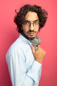 Beeindruckter junger hübscher kaukasischer mann, der brille und kopfhörer am hals trägt, der in der profilansicht steht, die kopfhörer lokalisiert auf purpurroter wand berührt