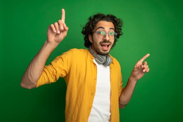 Beeindruckter junger hübscher kaukasischer mann, der brillen mit kopfhörern um den hals trägt, der kamera zeigt, die oben auf grünem hintergrund zeigt