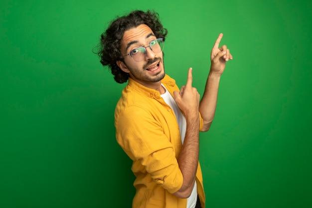 Beeindruckter junger hübscher kaukasischer mann, der brillen trägt, die in der profilansicht stehen und kamera betrachten, die lokal auf grünem hintergrund mit kopienraum zeigt