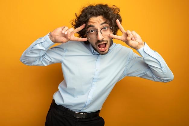 Beeindruckter junger hübscher kaukasischer mann, der die brille betrachtet, die kamera betrachtet, die hände nahe kopf hält, die friedenszeichen lokalisiert auf orange hintergrund tut