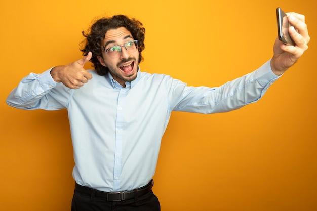 Beeindruckter junger hübscher kaukasischer mann, der die brille zeigt, die daumen zeigt, der selfie lokalisiert auf orange hintergrund nimmt