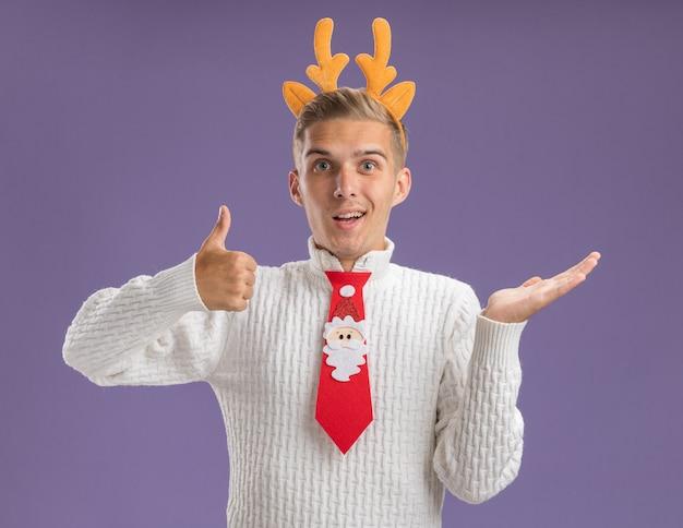 Beeindruckter junger hübscher kerl, der rentiergeweih-stirnband und weihnachtsmann-krawatte trägt und kamera betrachtet, die leere hand und daumen oben auf lila hintergrund zeigt