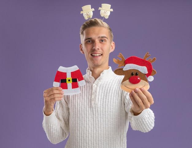 Beeindruckter junger hübscher kerl, der schneemann-stirnband trägt, das weihnachtspapierverzierungen in richtung kamera hält und ausdehnt, die kamera lokalisiert auf lila hintergrund betrachtet
