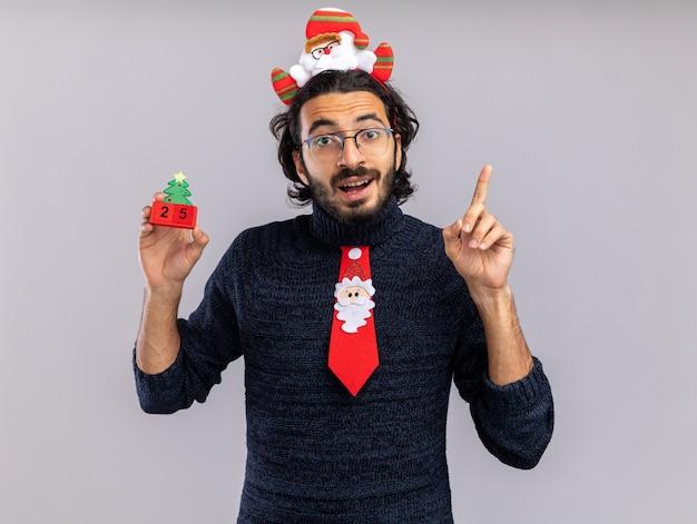 Beeindruckter junger hübscher kerl, der weihnachtskrawatte mit haarbügel hält, der weihnachtsspielzeugpunkte an oben auf weißem hintergrund hält